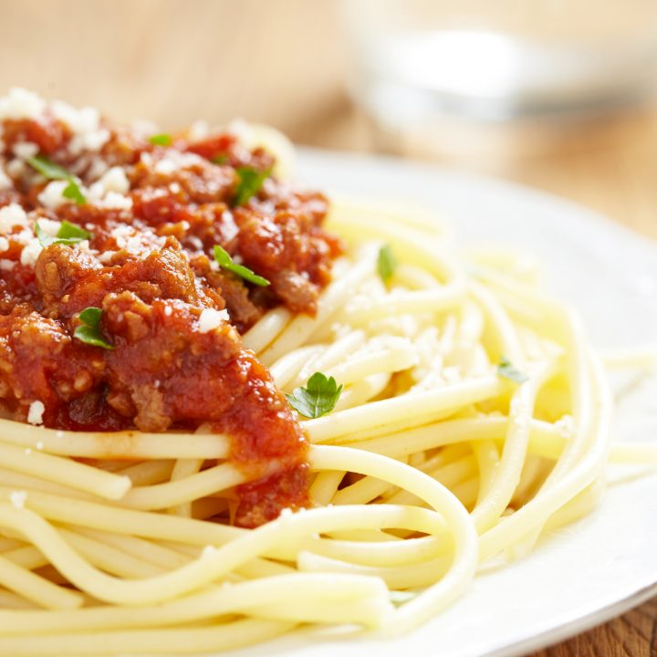 slow cooker bolognese served on a plate with spaghetti