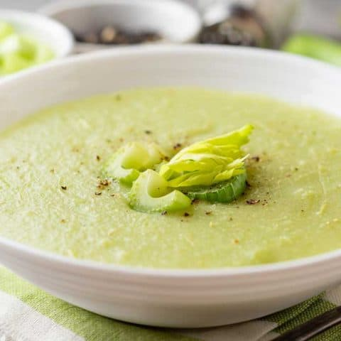 celery soup in a bowl with celery on top