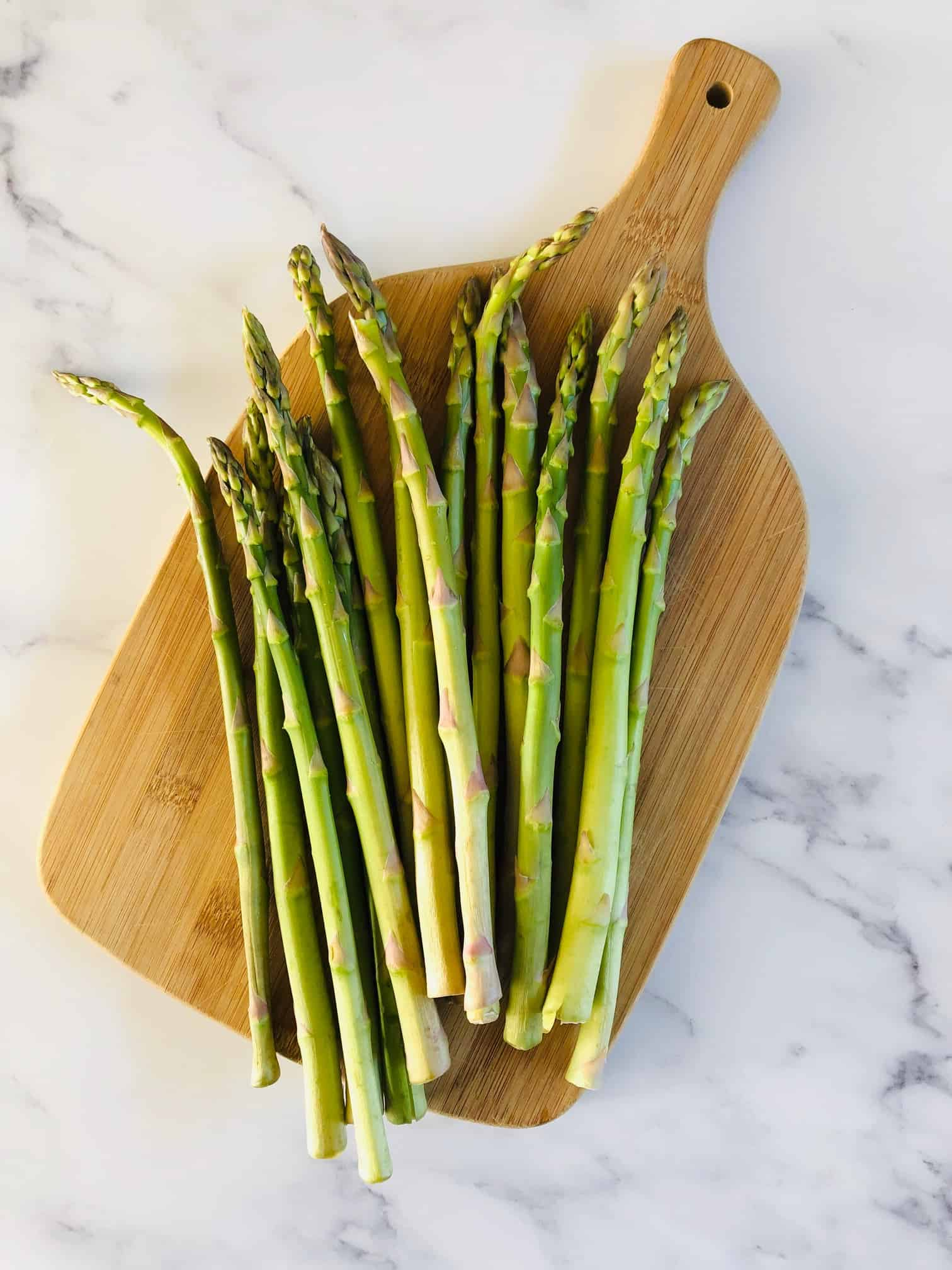 raw asparagus on a chopping board