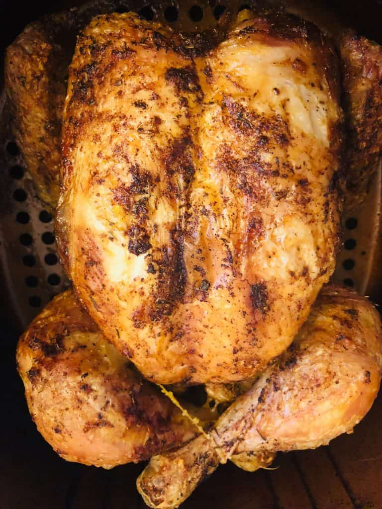 cooked whole chicken in an air fryer basket