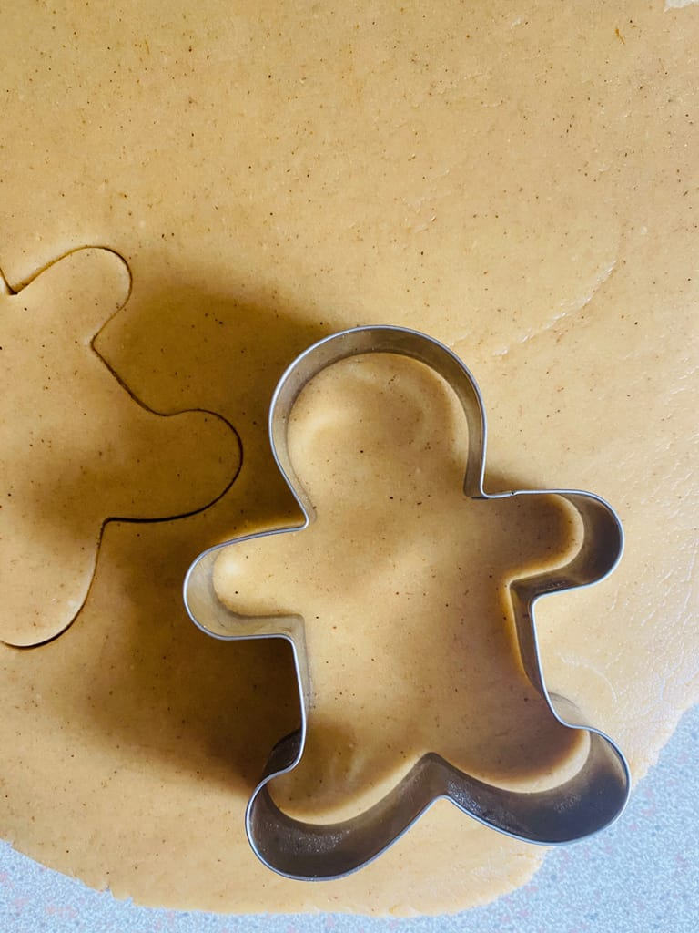 using a gingerbread man cutter to cut out cookie shapes from dough