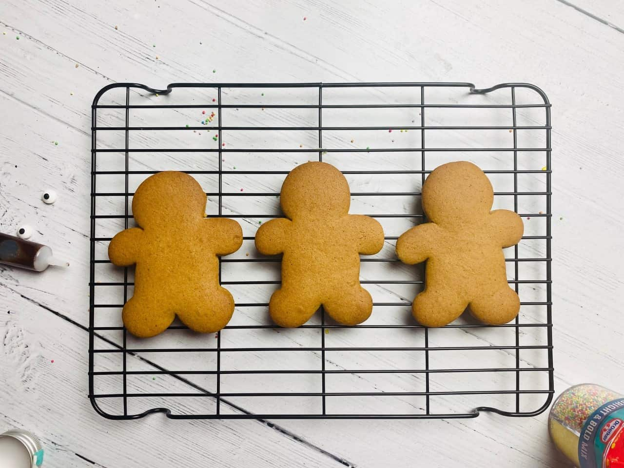 3 plain gingerbread men cooling down on a wire rack ready to be decorated