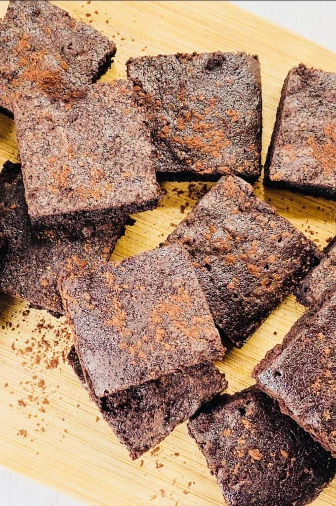 chopped up brownies on a chopping board with cocoa powder sprinkled on top