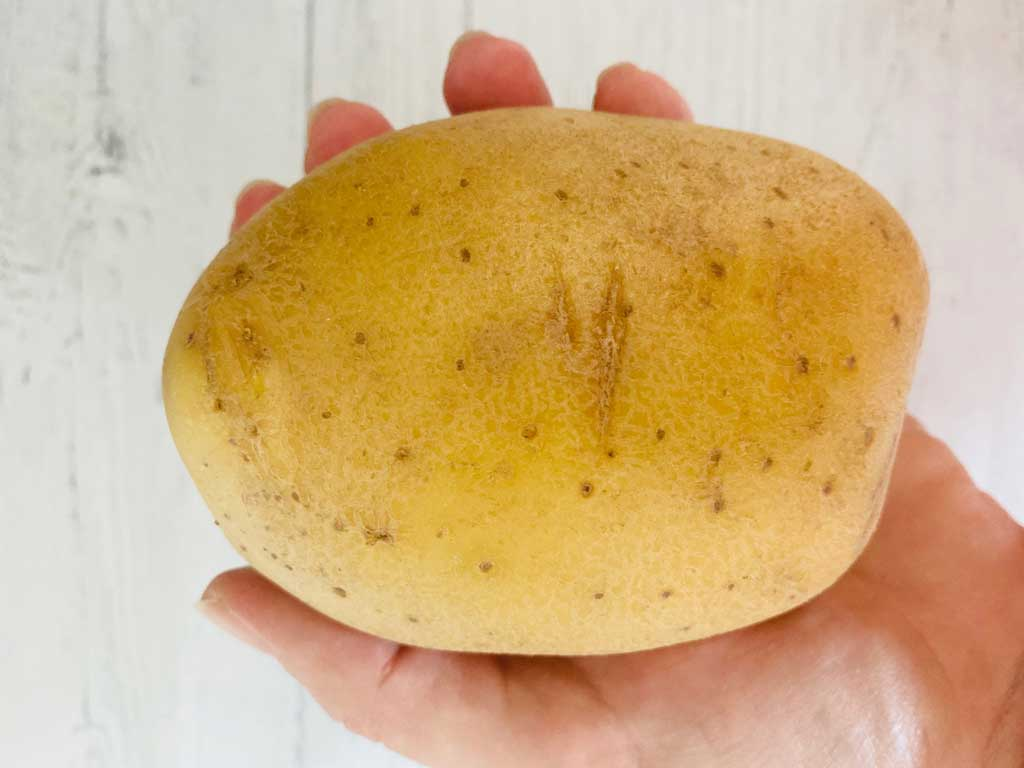 potato in hand for making jacket potato