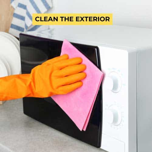 cleaning a microwave with a damp cloth