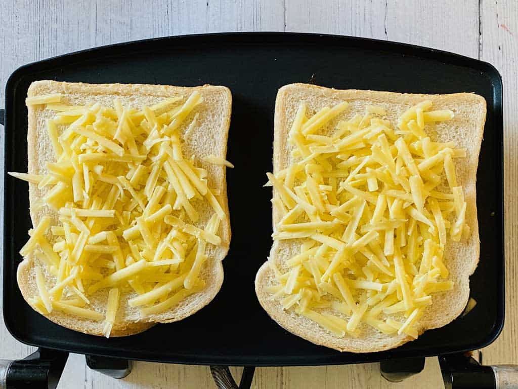 grated cheese on bread for ham and cheese toastie