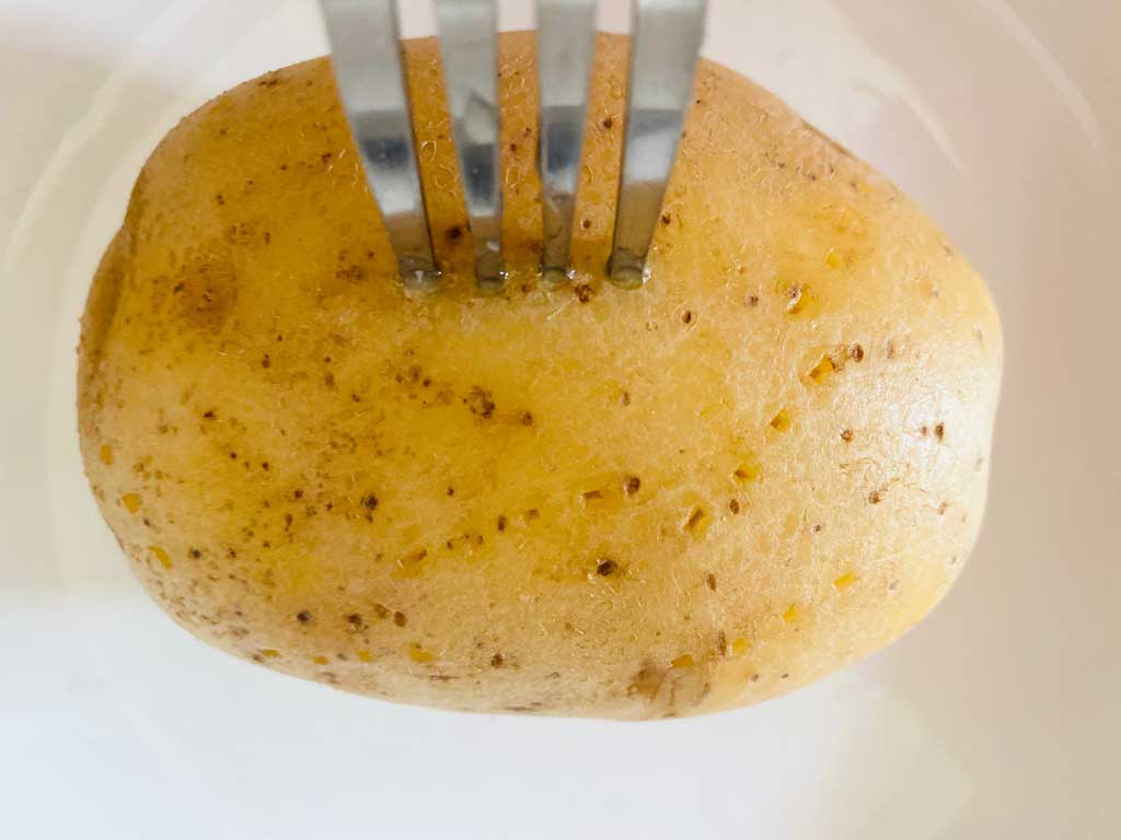 fork piercing baked potato before cooking in microwave