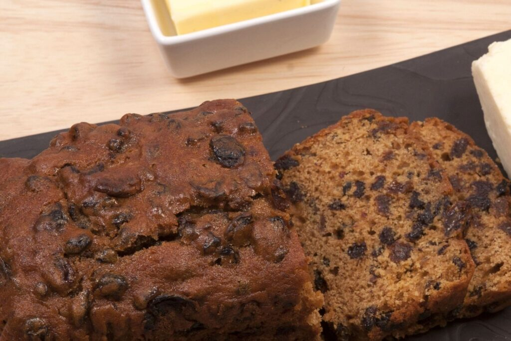 Bara Brith sliced up with butter next to it