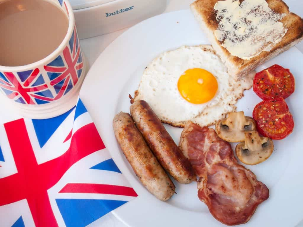 Full English breakfast next to a Union Jack flag and cup of tea in a Union Jack mug