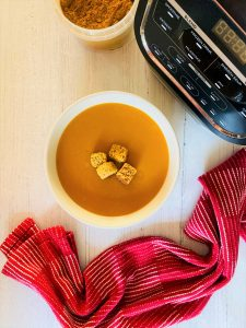 spiced carrot soup next to Ninja soup maker and red tea towel and curry powder in a pot