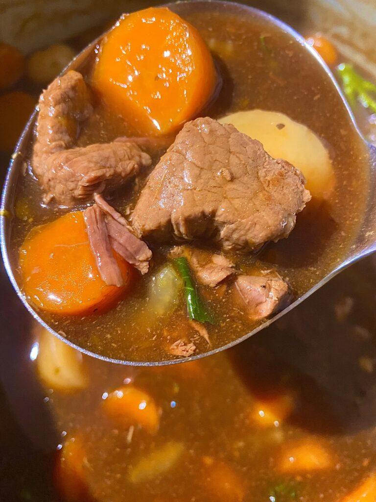 Serving spoon holding beef stew above Ninja Foodi