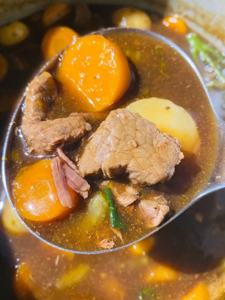 serving spoon with beef stew just cooked in a Ninja Foodi, beef, carrots, potatoes, gravy and broccoli in a beef gravy.