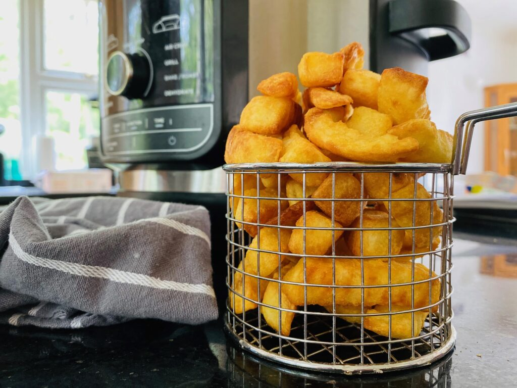 frozen chips cooked in the air fryer and placed in a wire serving basket next to the Ninja Foodi