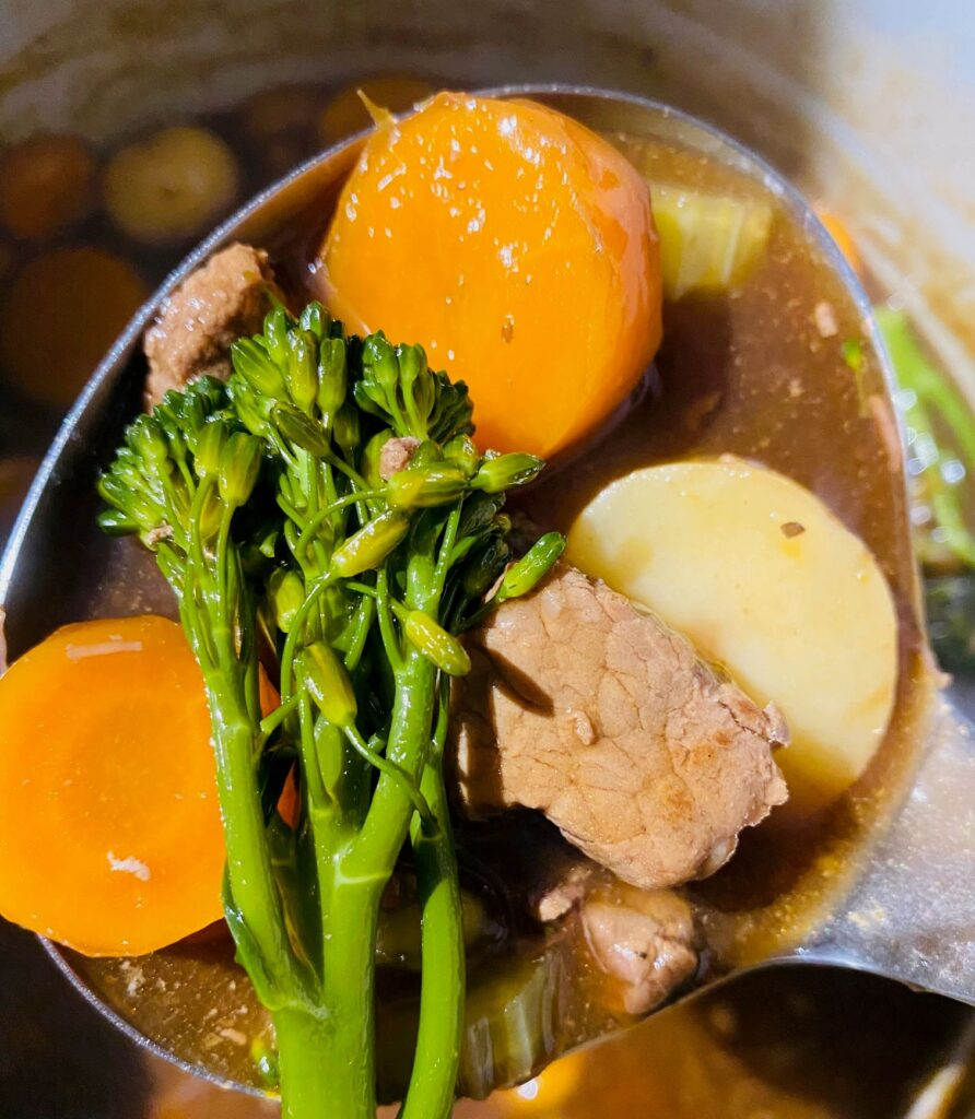 serving spoon holding beef stew just cooked in the Ninja Foodi, beef, broccoli, carrots, potato and gravy