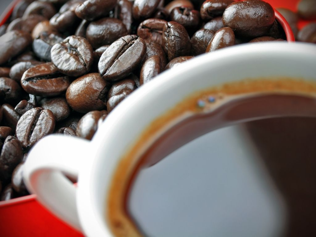 coffee beans next to a cup of coffee