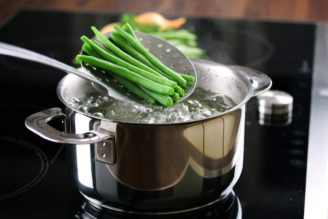 runner beans above saucepan of boiling water for blanching