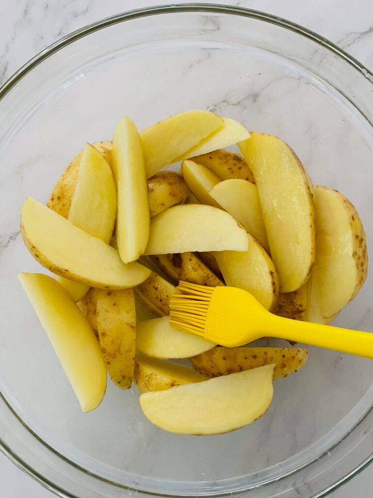 oiling potato wedges with a brush before adding them to the Ninja Foodi Air Fryer