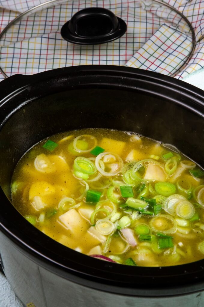 cover chopped leek and potato soup in slow cooker with stock