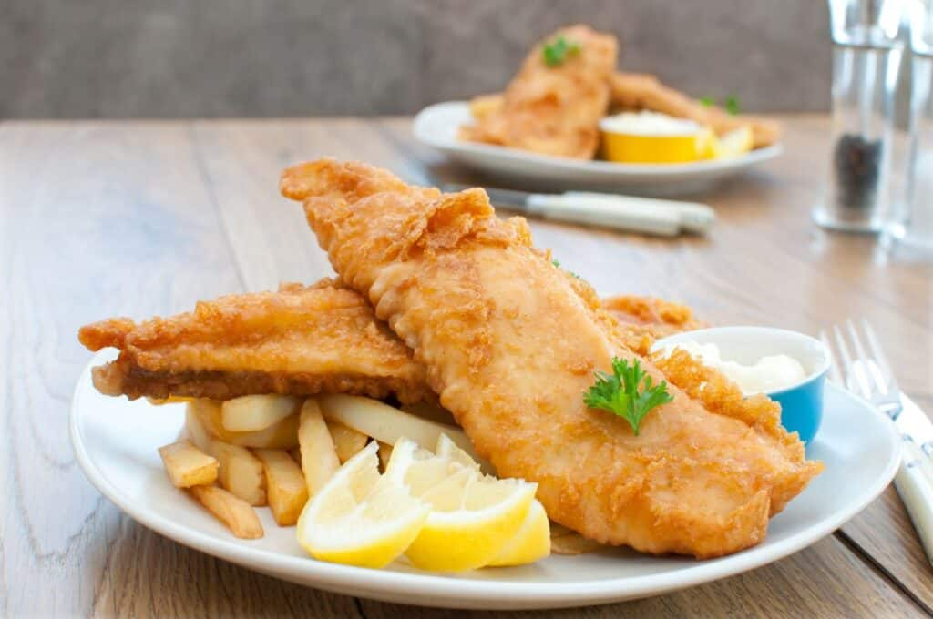 battered fish and chips on a plate with lemon slices