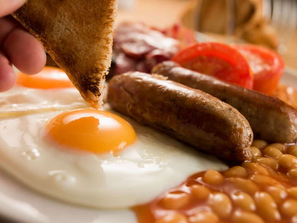 full English breakfast with fried egg, sausages, baked beans, tomatoes and toast being dipped in