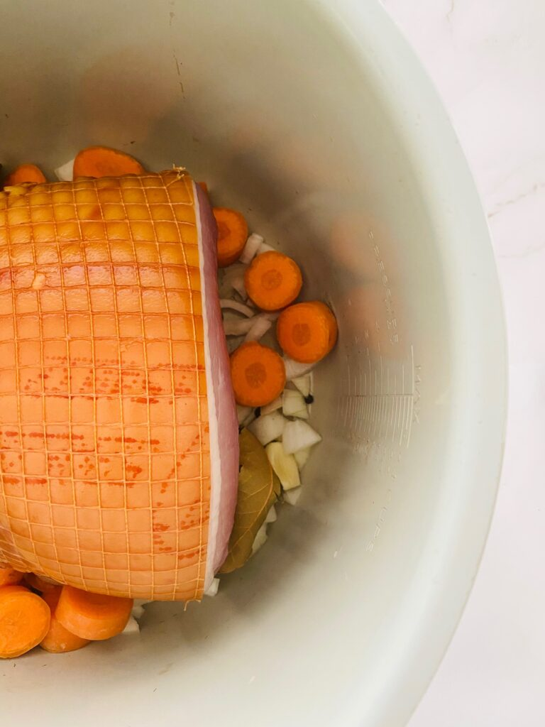 uncooked gmamon joint in Ninja Foodi pot with chopped carrots and chopped onions