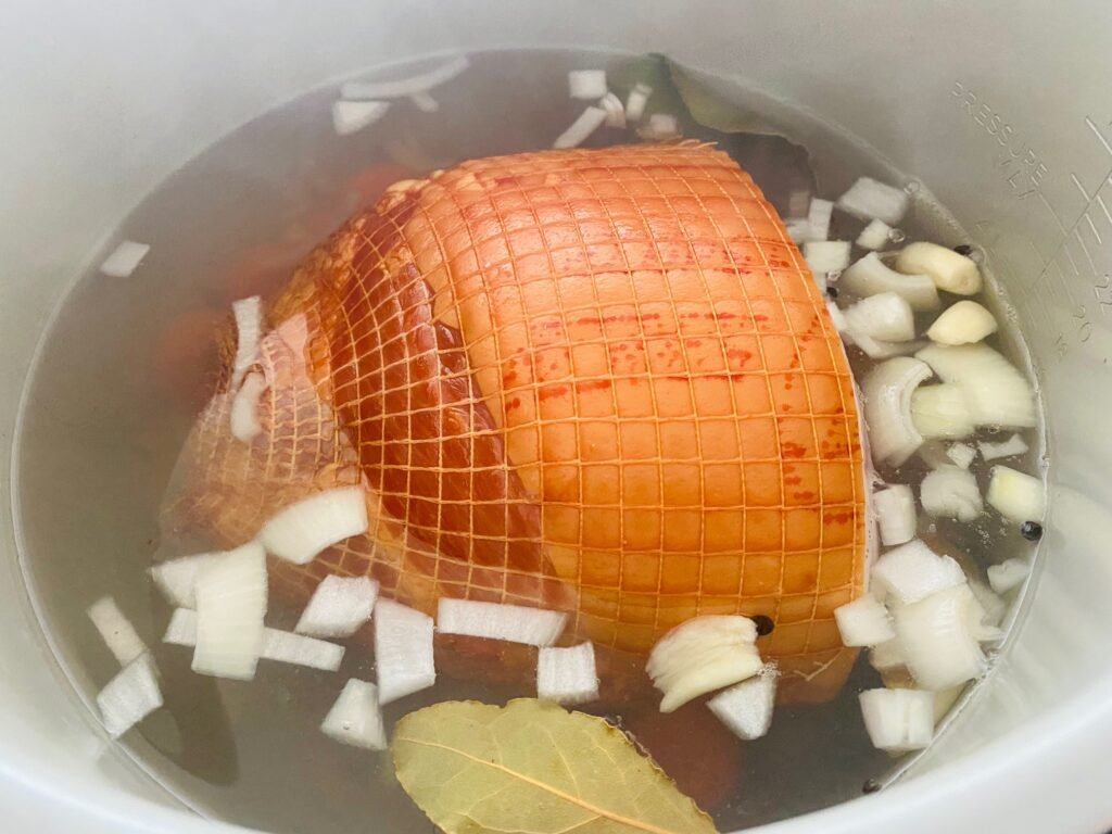 gammon joint in Ninja Foodi pot with water, chopped onions and bay leaves