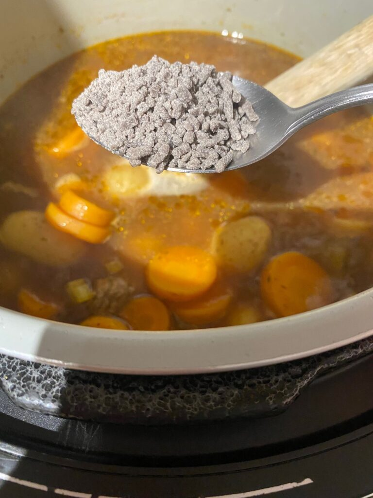 stirring gravy granules into pressure cooker beef stew in Ninja Foodi