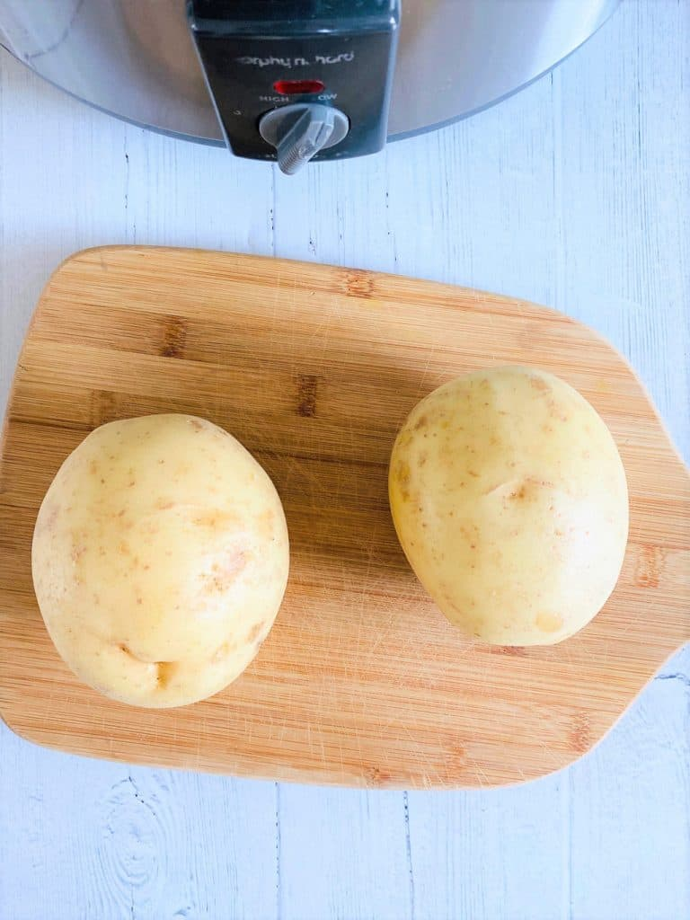 baking potatoes on chopping board next to slow cooker