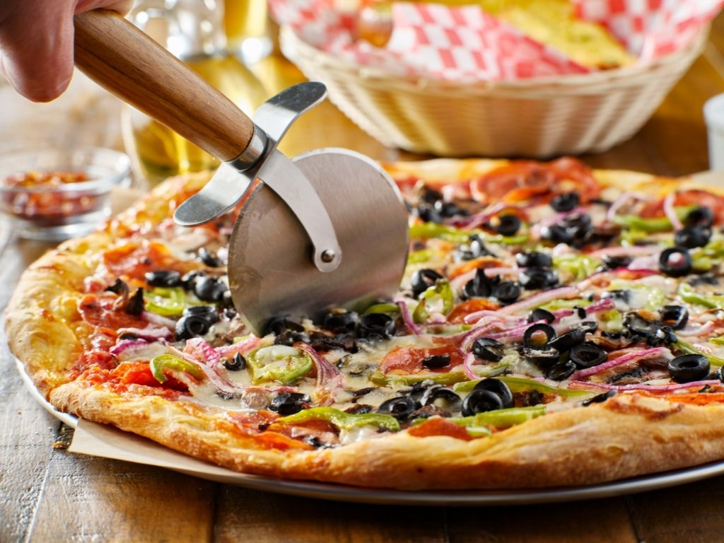 pizza cutter cutting a pizza