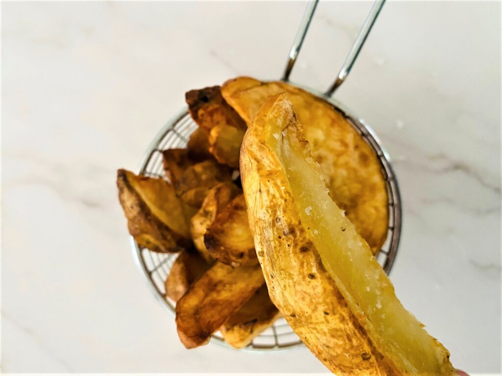 air fryer cooked potato wedge slice above basket of more air fried potato wedges