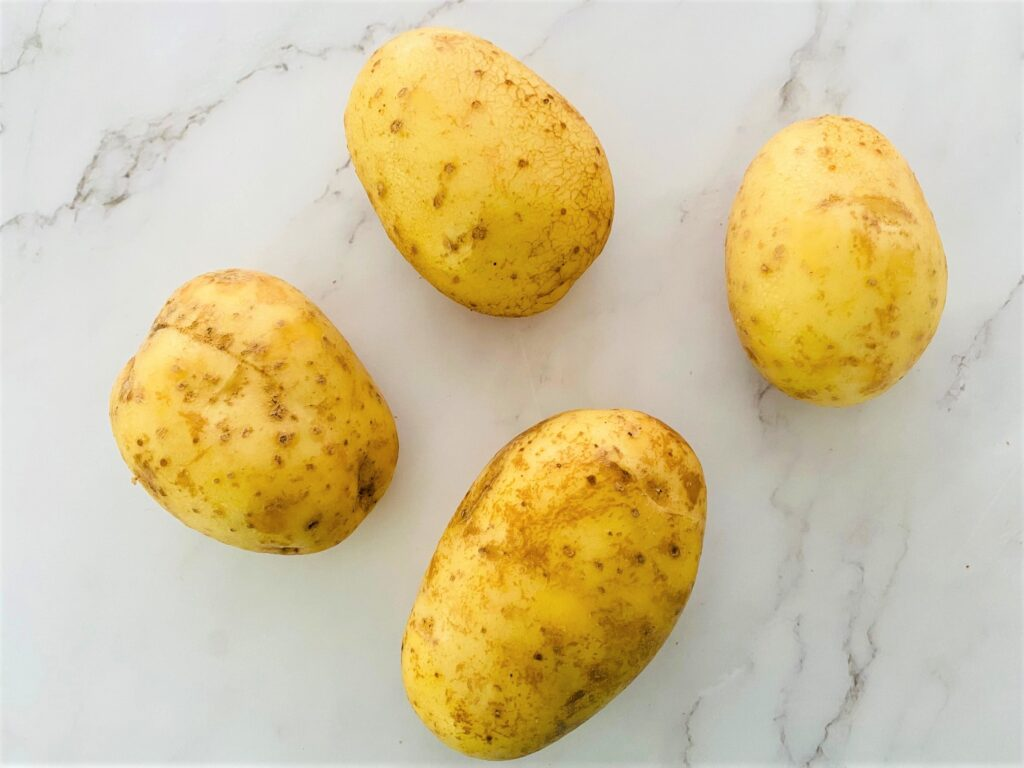 4 Maris Piper potatoes with skin on, cleaned ready to be cut into potato wedges for cooking in an air fryer
