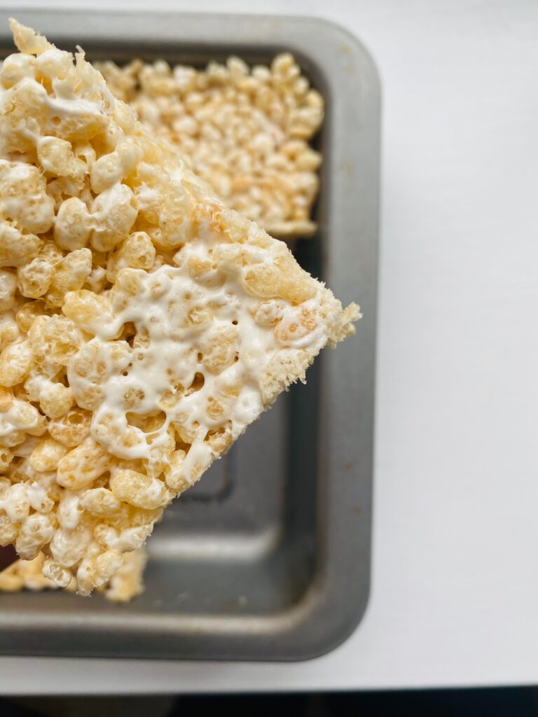 Rice Krispie Marshmallow Treats in baking tray with one cut out and held up