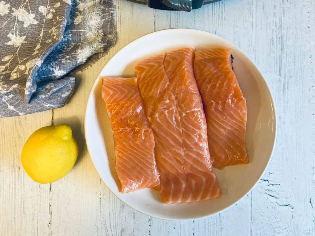 4 slices of raw salmon next to a lemon and slow cooker