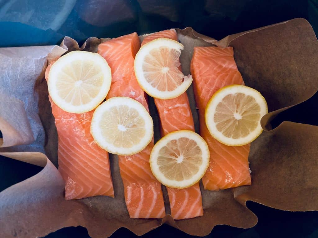 salmon on baking paper with lemons on top in a slow cooker