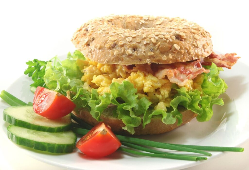 bagel with scrambled egg bacon and salad