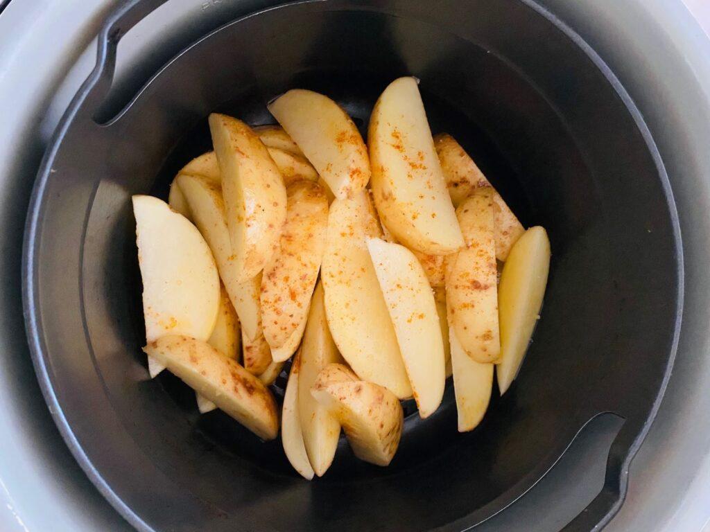 seasoned potato wedges sitting in the Ninja Foodi air fryer basket