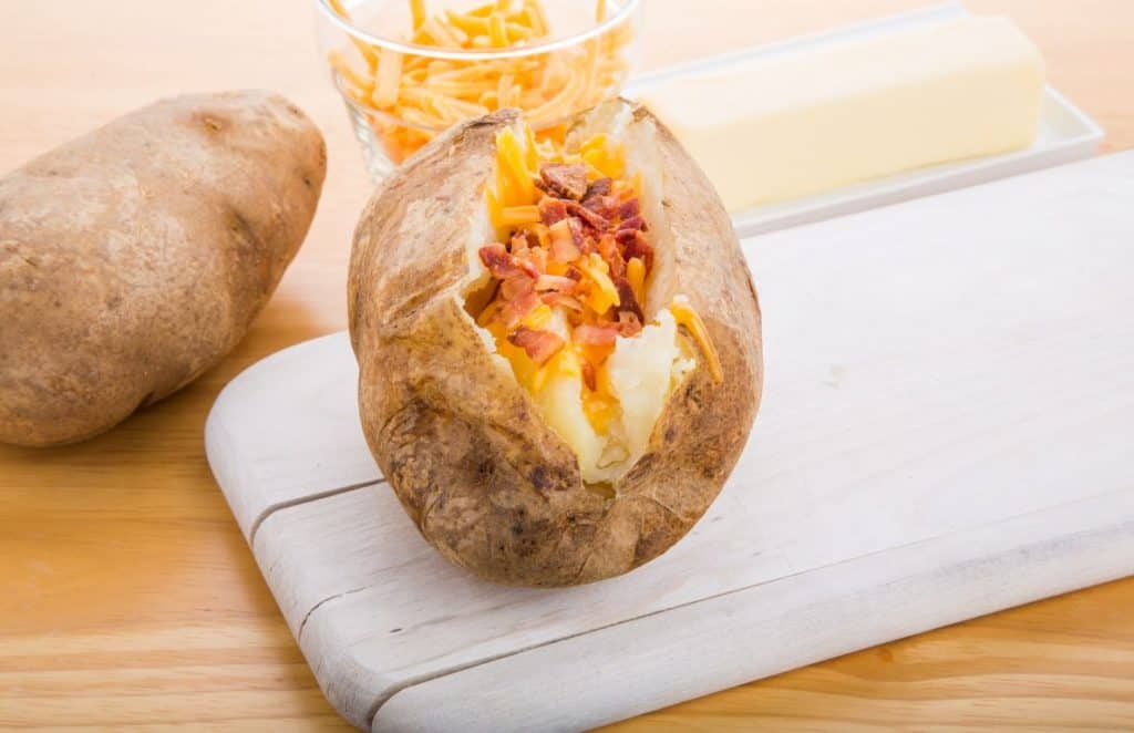slow cooker jacket potatoes with cheese and bacon topping