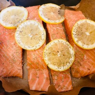 slow cooker salmon with sliced lemons and dried herbs on top