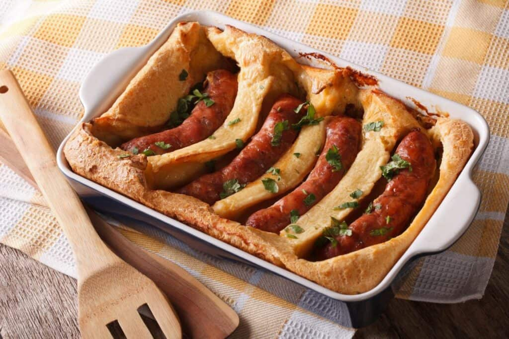 toad in the hole in an oven dish on yellow and white tablecloth