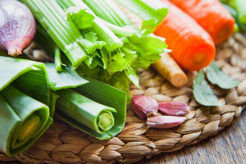 vegetable stock ingredients - onions, celery, carrots, bay leaves, garlic cloves, leeks